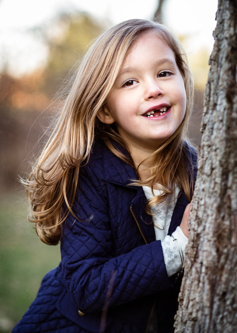 Sweet brunette girl smiling at camera next to a tree.