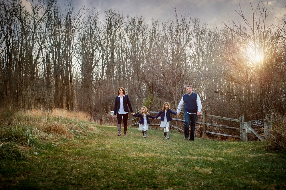 Family of four walking together in park backlit by sunset.