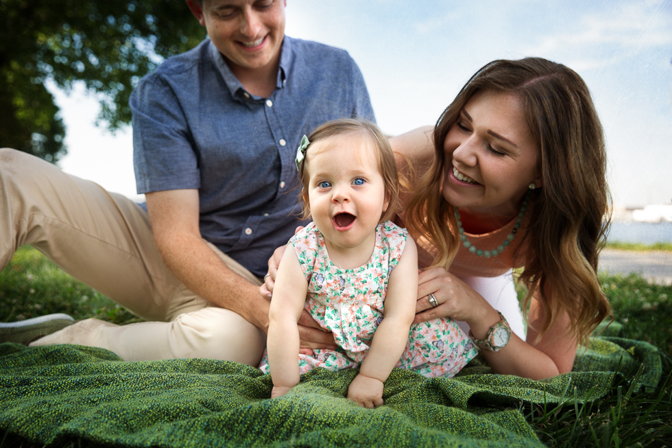 Baby's dress leaves no room for doubt that she is the focal point of the image and this family's center of attention.