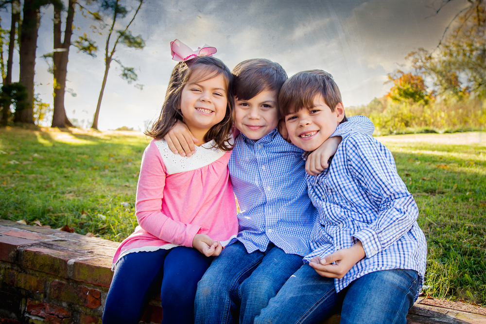Twin boys in blue plaid shirts sit on a stone wall with their adorable sister. All are smiling at the camera.