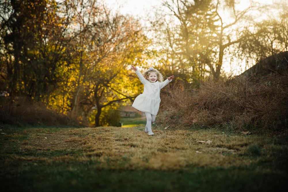 Girl running through field among golden leaves in white dress.