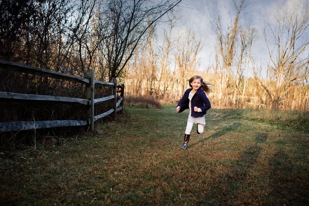 Young girl in blue coat and grey dress running by a fence in Hunt Valley, MD park.