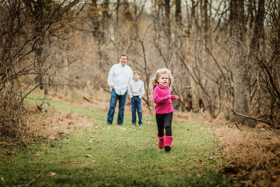 Girl in pink top and boots running with father and brother in background watching.