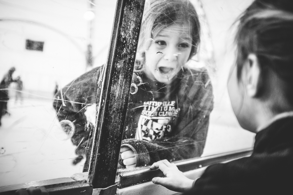 girl smiling at sister through ice rink glass wall.