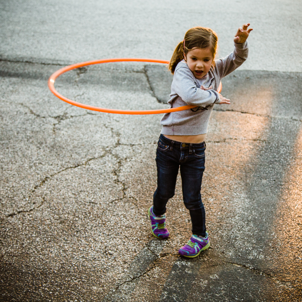 child with pig tails playing in the street.