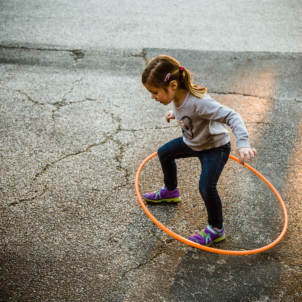 Young brunette girl jumping over orange hula hoop.