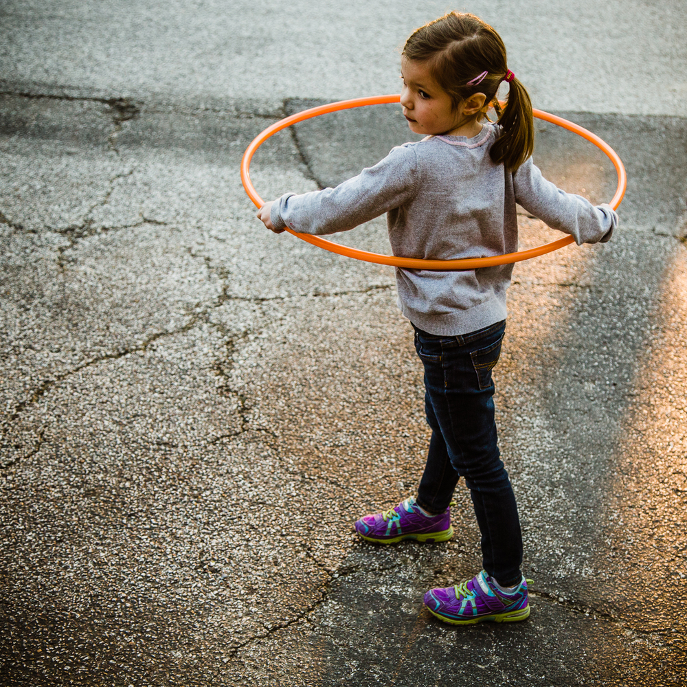Girl with orange hula hoop.