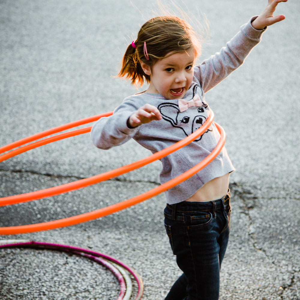 Girl making silly face while wiggling with hula hoop