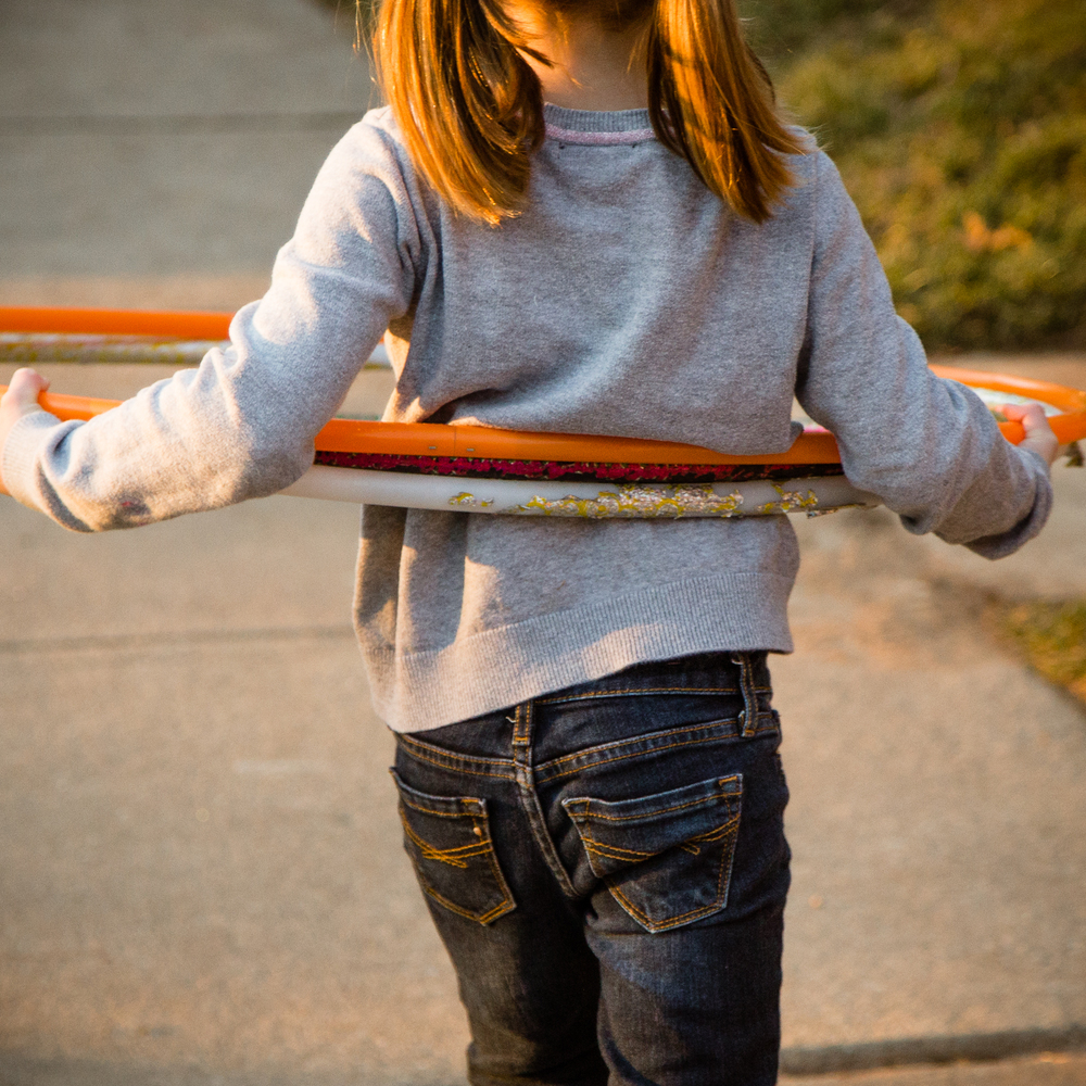 photograph from behind of girl carrying several hula hoops with golden sunlight