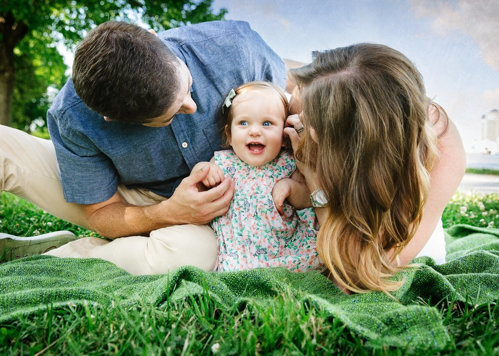 Mom and dad adore their young daughter in family portrait taken on grass in Fort McHenry, Baltimore City.