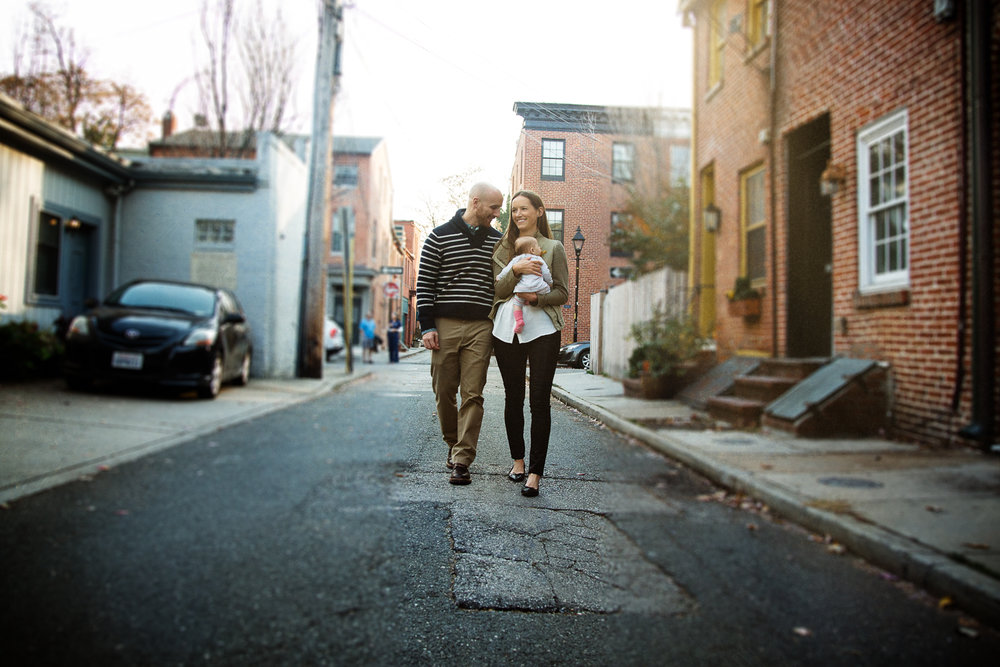 Young parents walk with their newborn daughter in Fells Point, Baltimore.