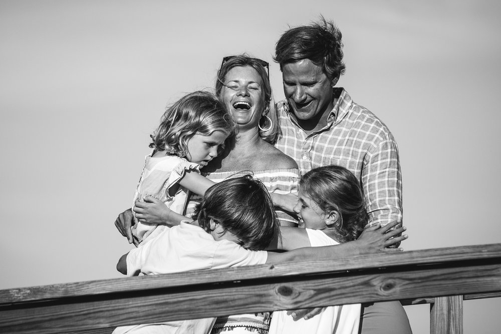 gorgeous young family of five smiling in beach family portrait hugging each other