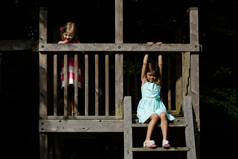 sisters playing on a swings in harsh sunlight.