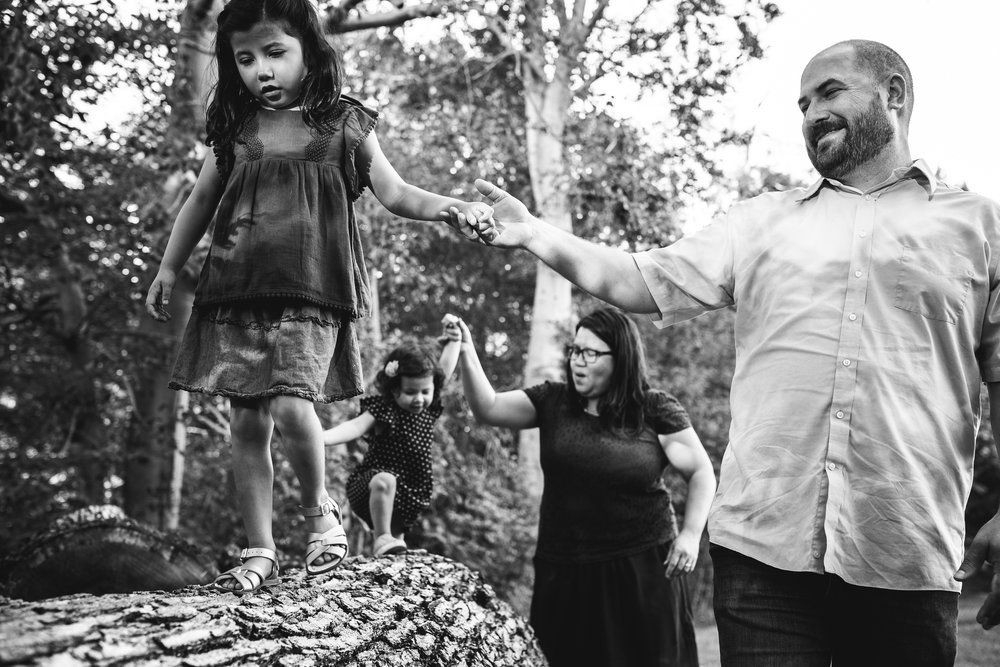 parents help their daughters walk across log in black and white photograph