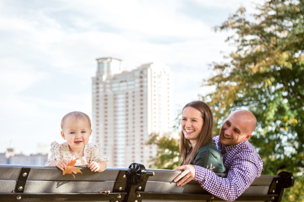 father and mother admire one year old daughter smiling at camera on park bench