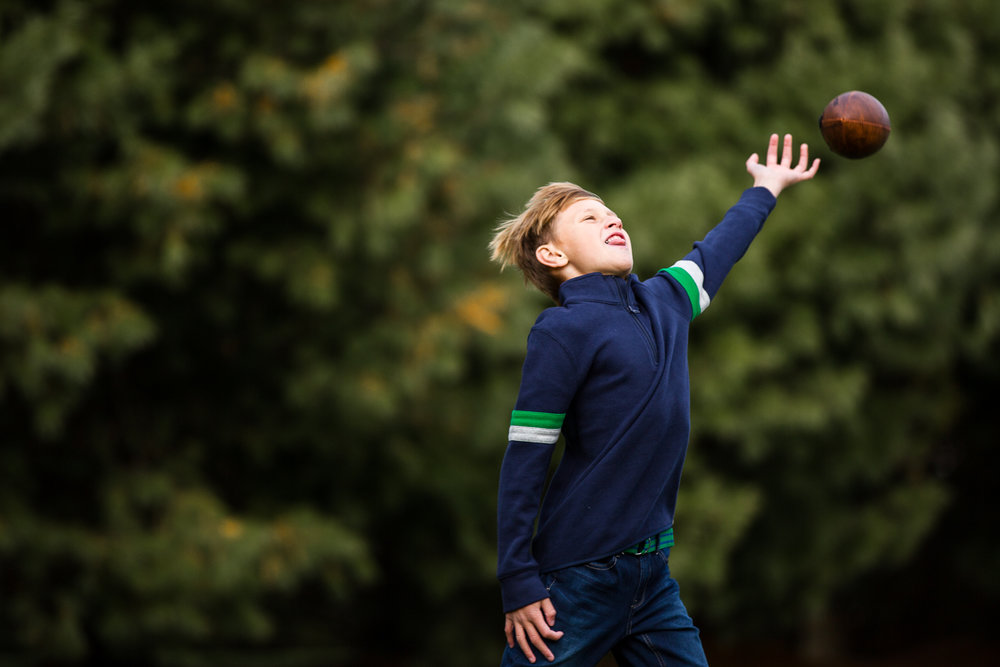boy in blue sweater reaching to catch ball