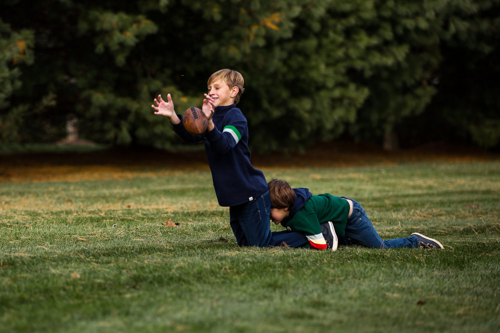 boy catching football in back yard