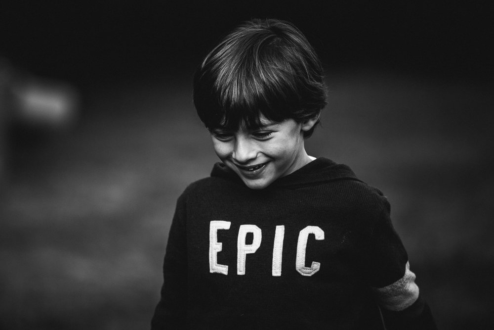 black and white photo of boy wearing sweater that says EPIC