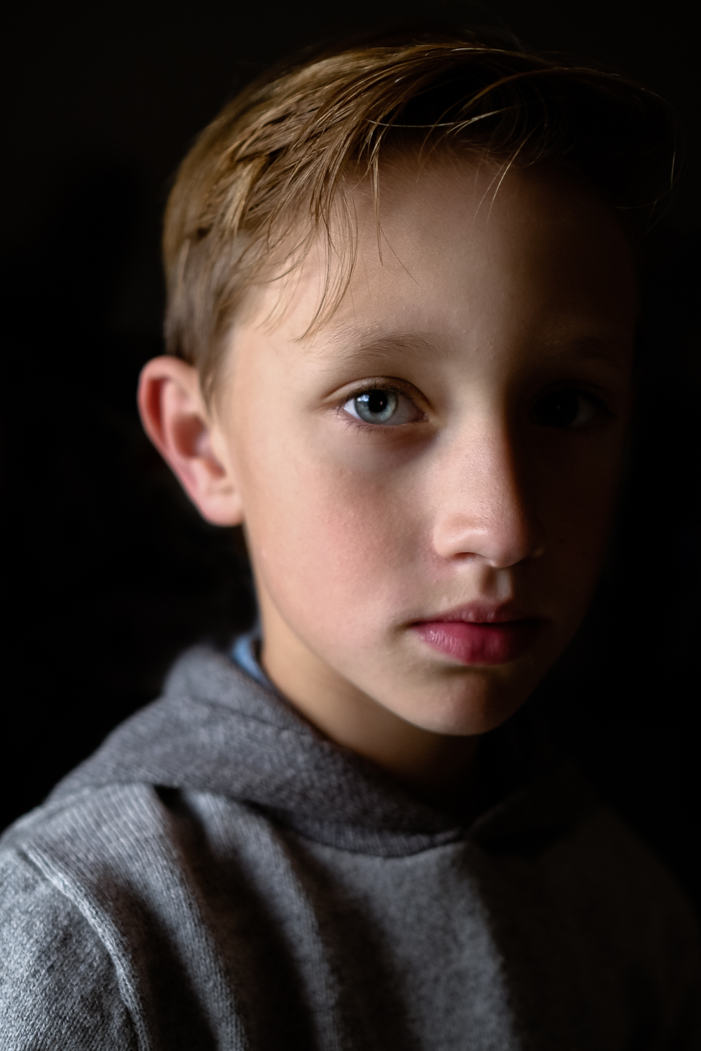 side lit portrait of blonde young boy