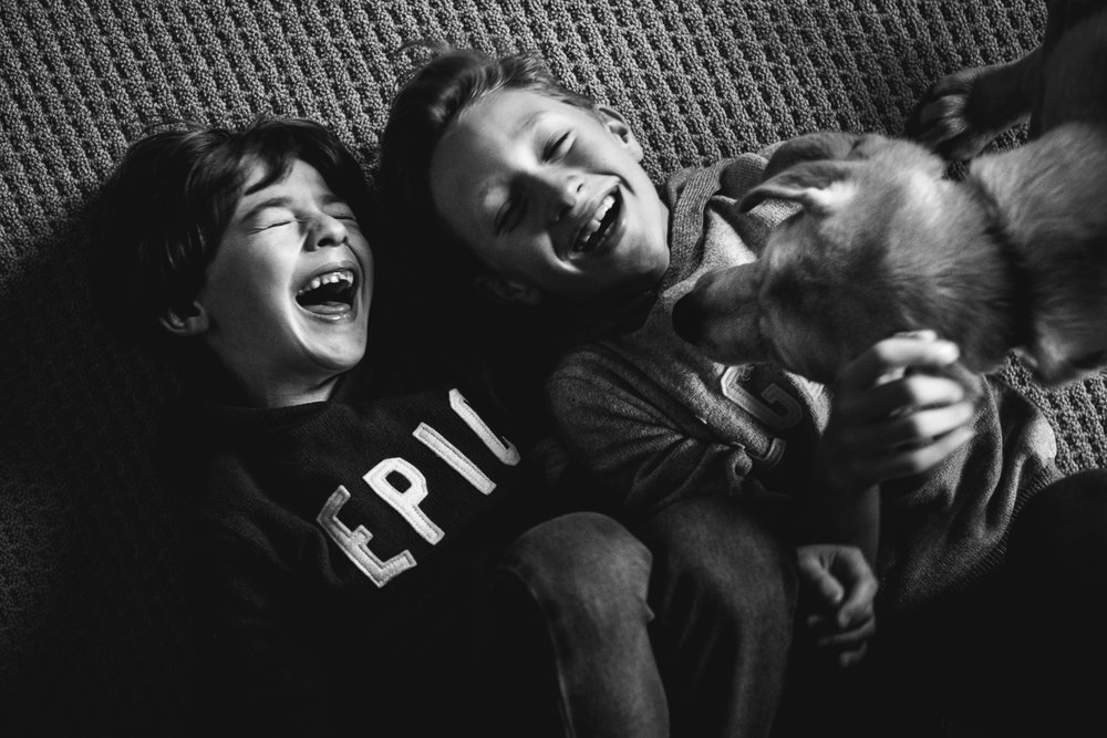 black and white photograph of boys on floor playing with their dog.