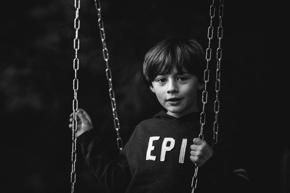 boy in tire swing holding chains
