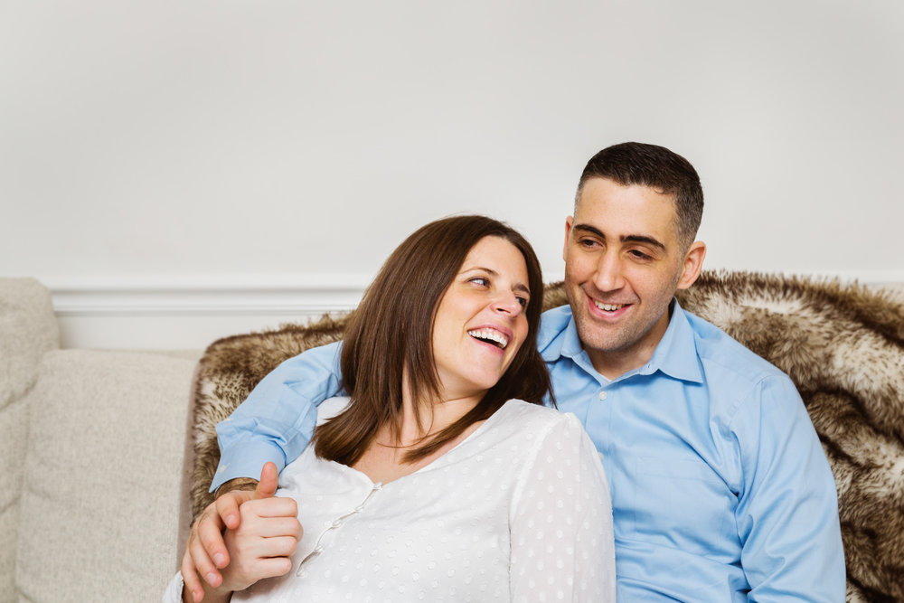 expectant parents snuggle on sofa
