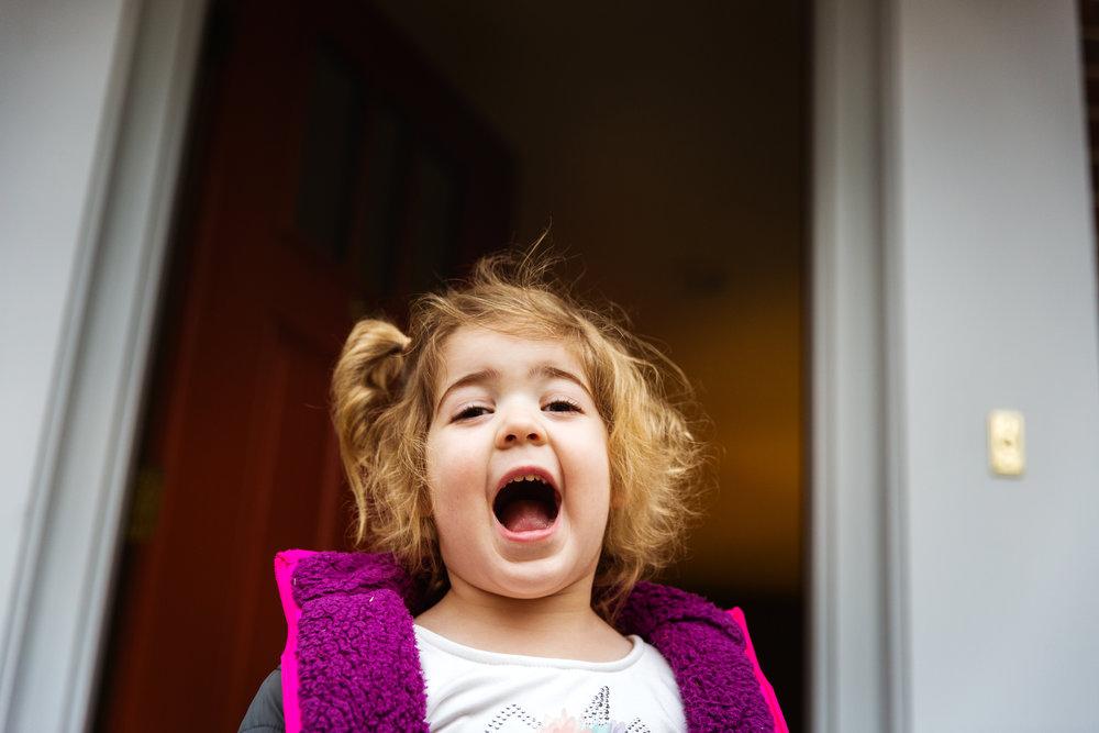 little girl in pink jacket smiles in doorway to her family home