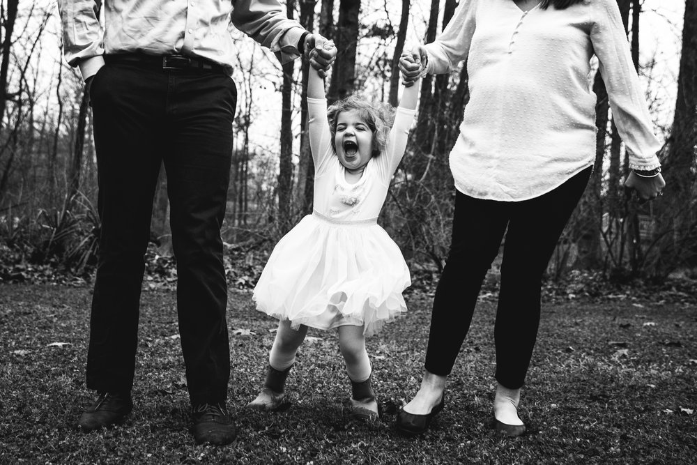 little girl in tutu hold's parents hands with big smile in black and white photograph