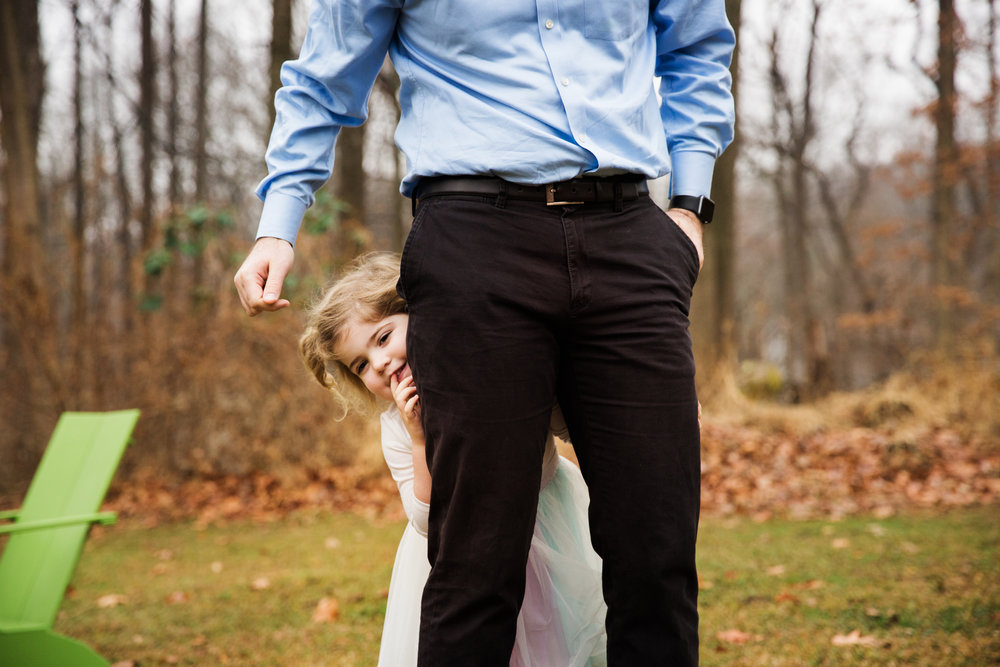 two year old girl peeks out from behind her dad's legs