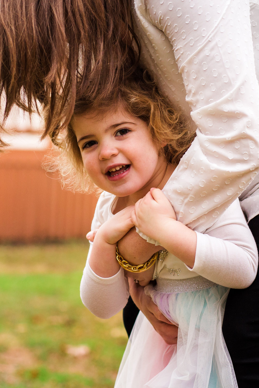 girl smiles at camera while holding mothers arms