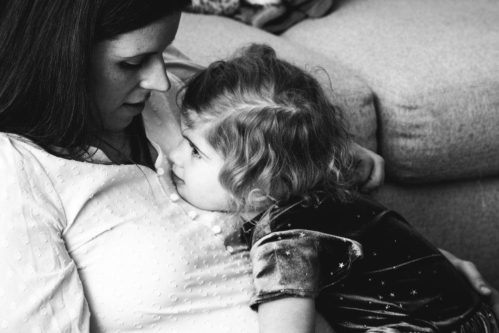 little girl snuggles with her mother in black and white family photo