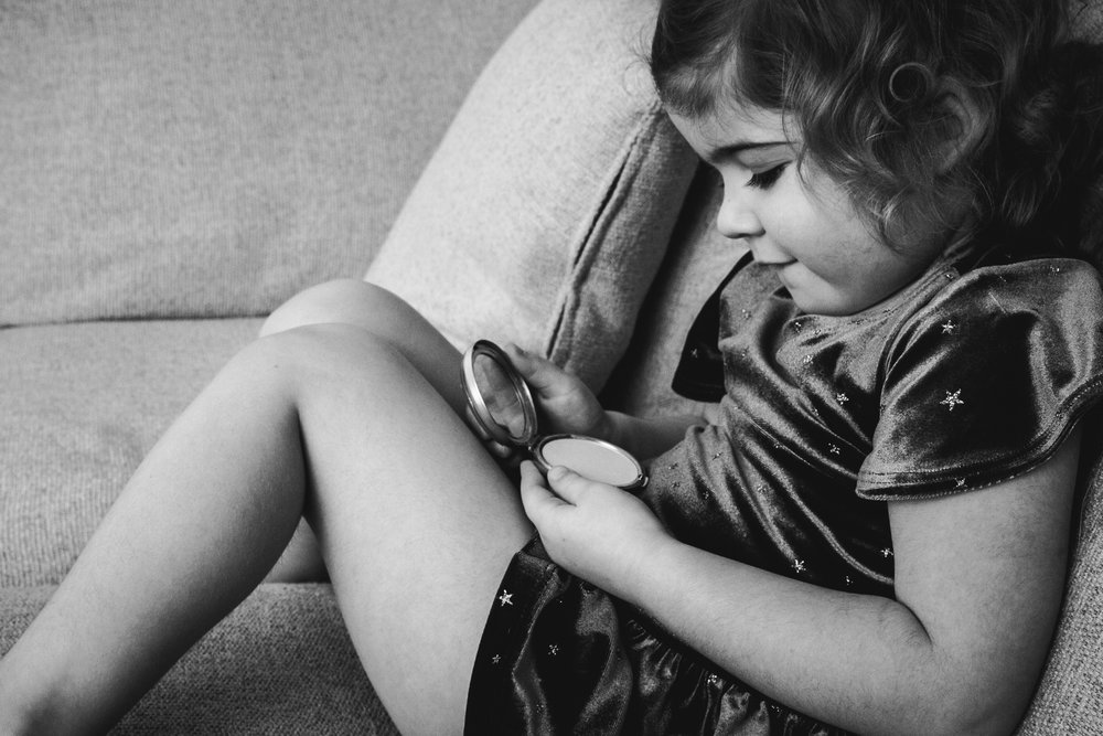 black and white photograph of little girl looking at compact mirror