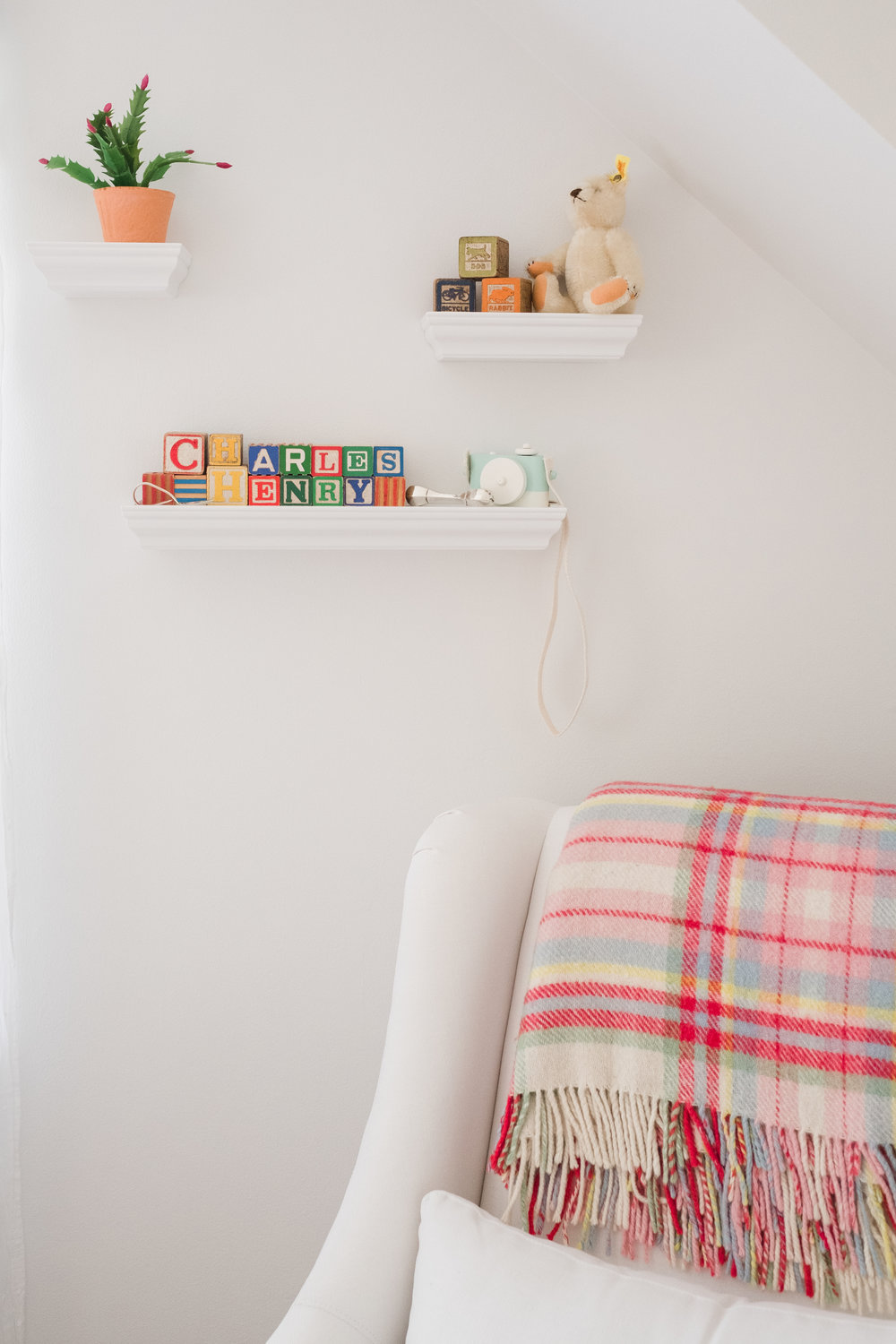 view of colorful blanket draped over white chair in baby boy nursery