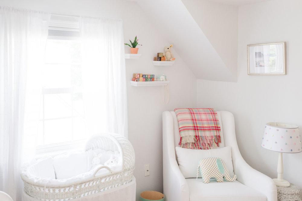 bassinet by nursery window in baby boy's room