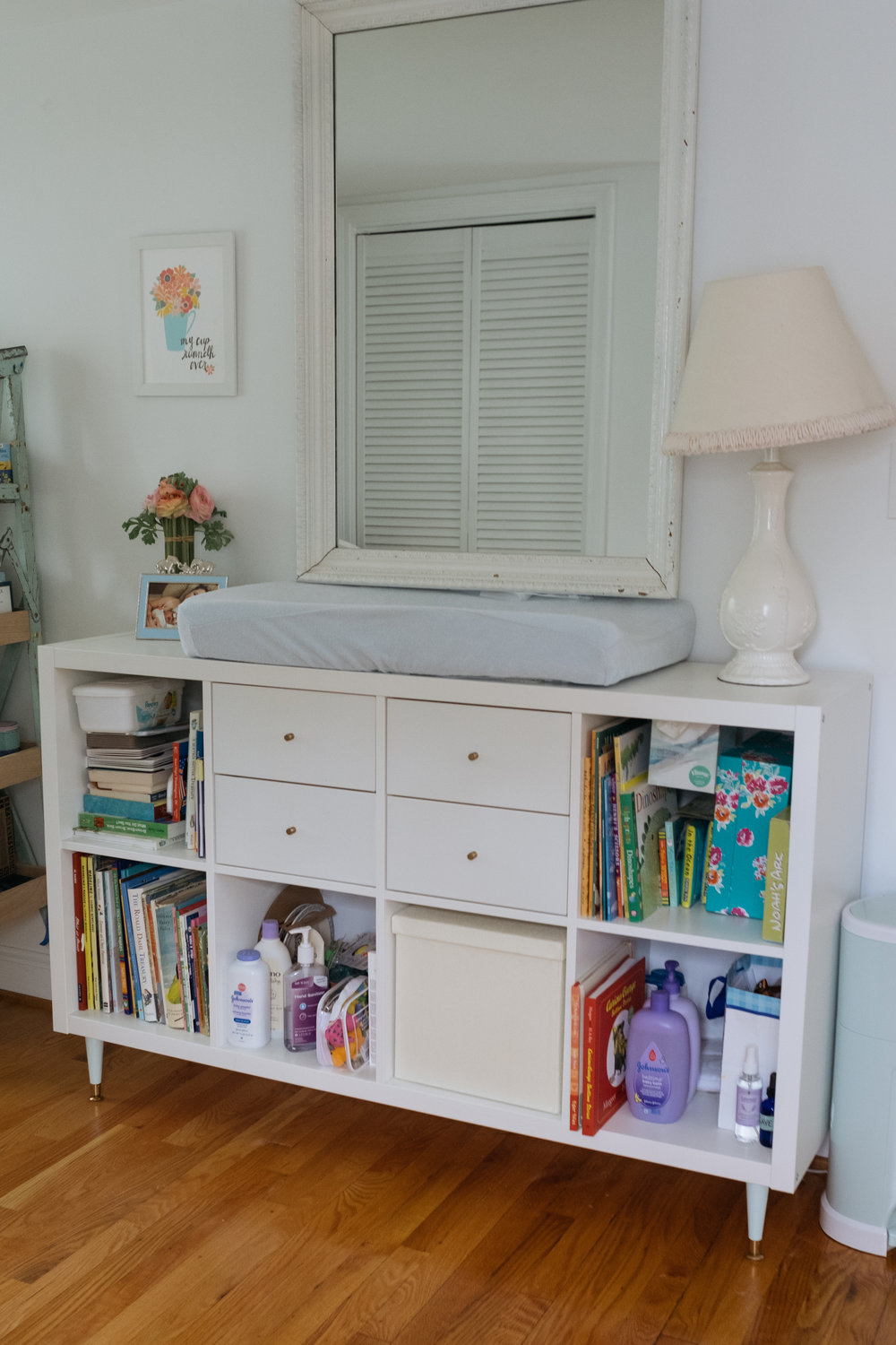 space in baby boy bedroom with dresser and changing table and antique mirror