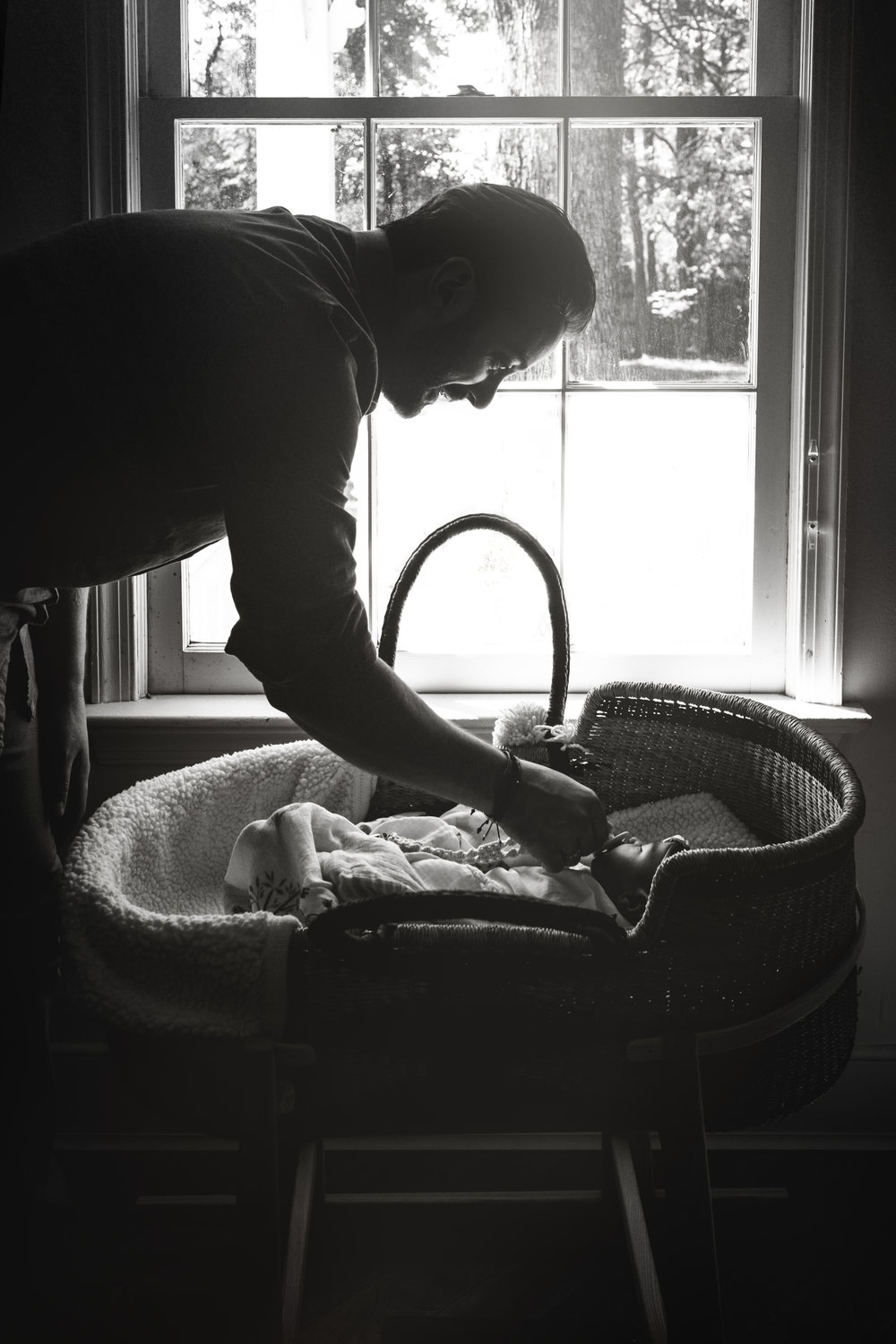 black and white silhouette photograph of father tending to baby daughter in bassinet