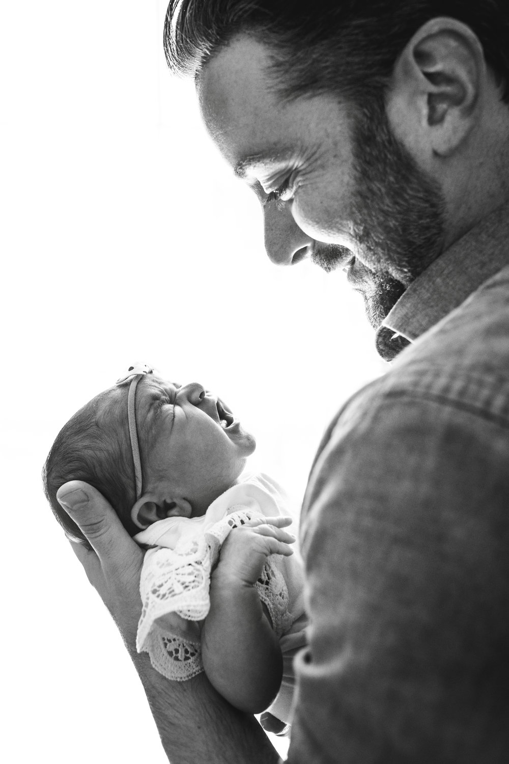 black and white photograph of father smiling at crying baby girl