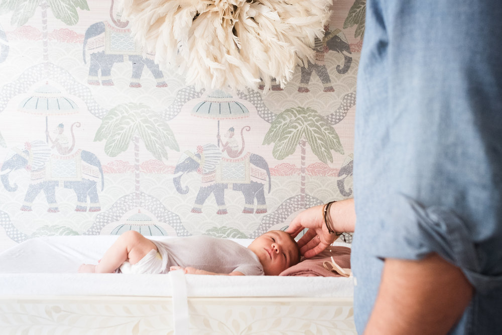 father plays with infant daughter on nursery changing table