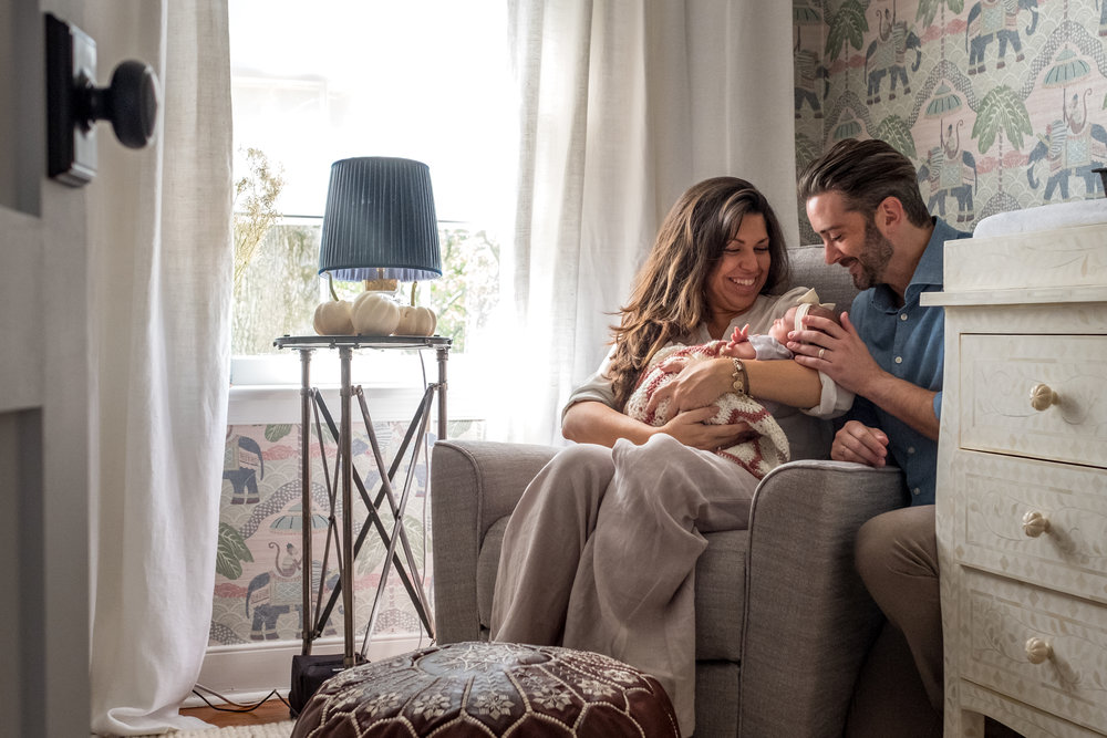 parents sit in chair in nursery by window and smile and hold their newborn daughter in candid portrait