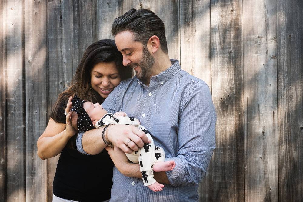 outside portrait of parents holding newborn baby daughter by wood doors of garage