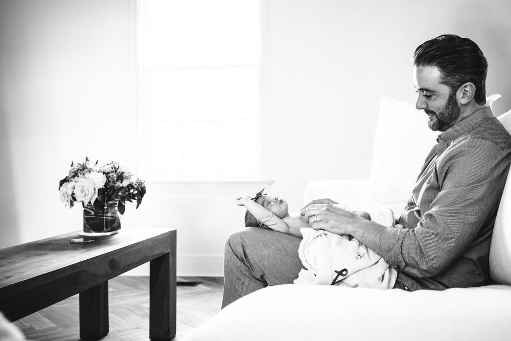 dad plays with his new baby daughter while sitting on sofa by a window