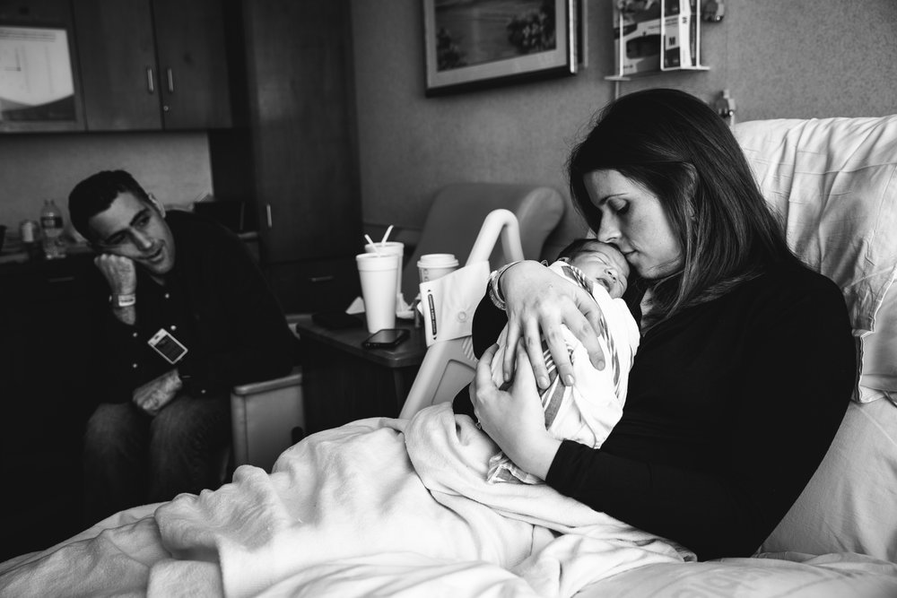 new mother snuggles and kisses infant son in hospital while baby's father looks on in background.