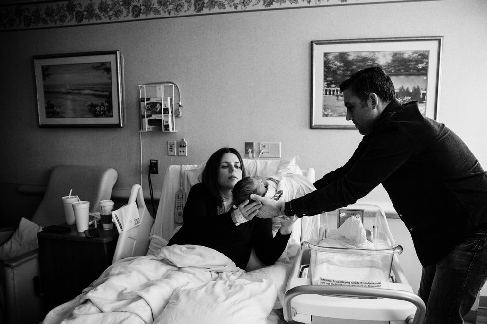 mother in postpartum hospital room holds newborn son with father looking on