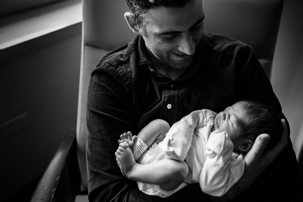 black and white photograph of father smiling at his infant son in Baltimore hospital room