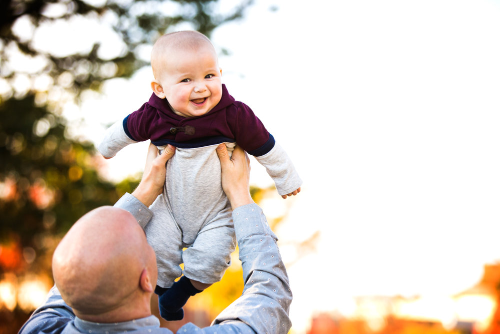 photograph taken while dad holds grinning baby son up in the air
