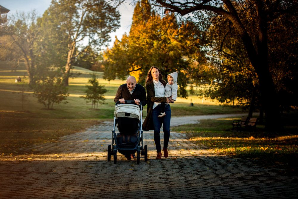 family of four with stroller walking through Baltimore park path in fall