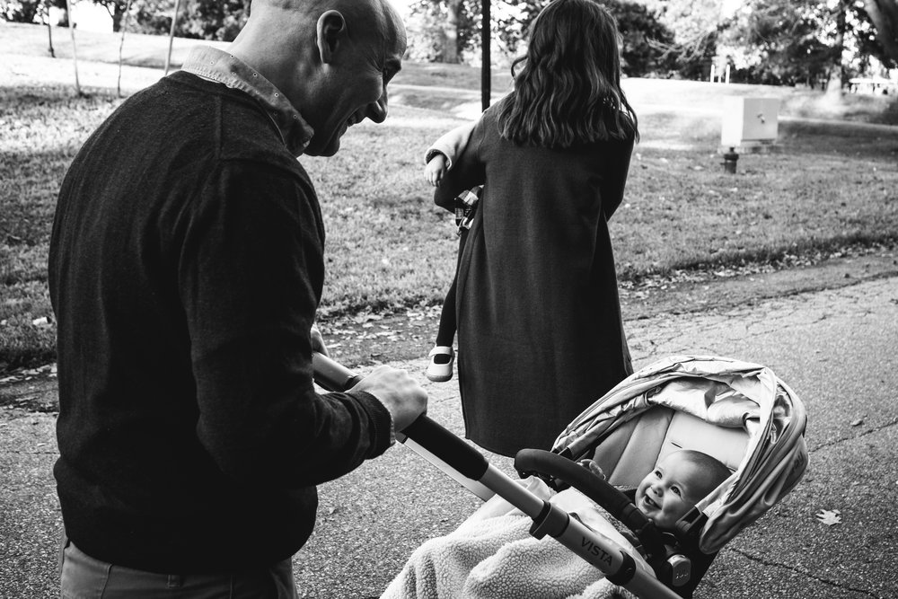 black and white photograph of dad peeking at baby son in stroller