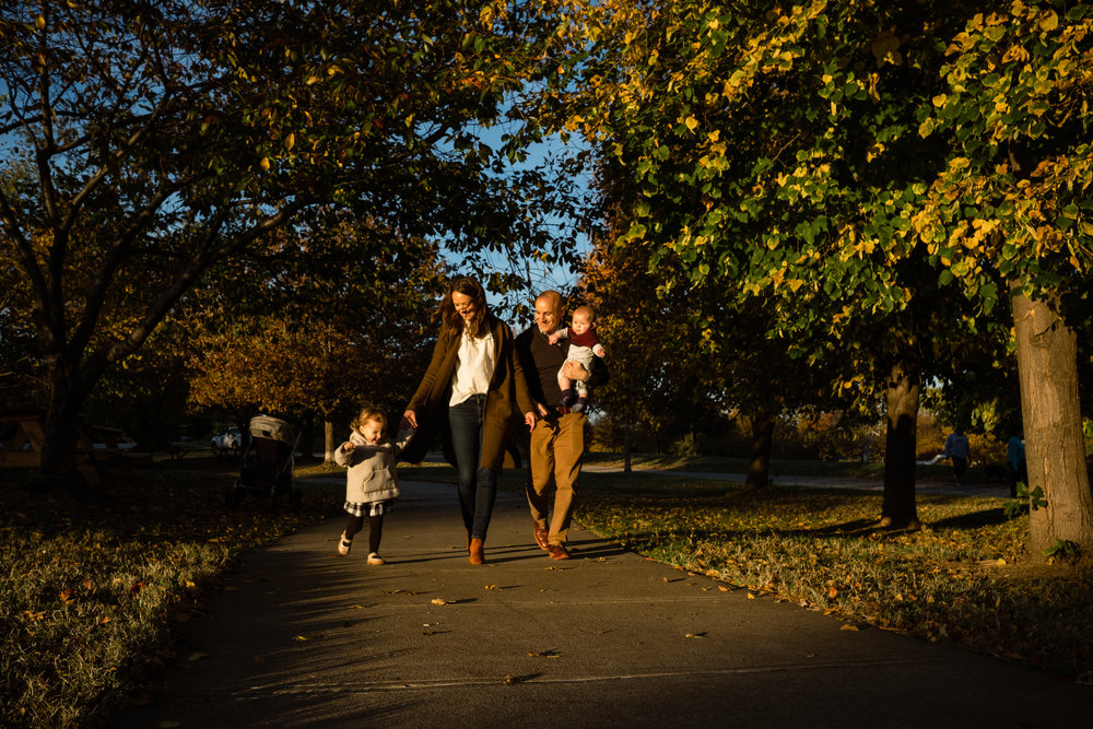sweet young family with two children walks along golden lit park path
