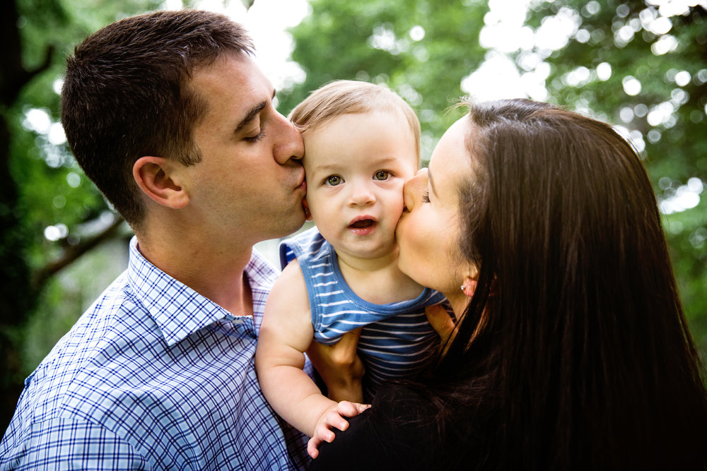 loving parents kiss the cheek of their little boy as he looks at the photographer