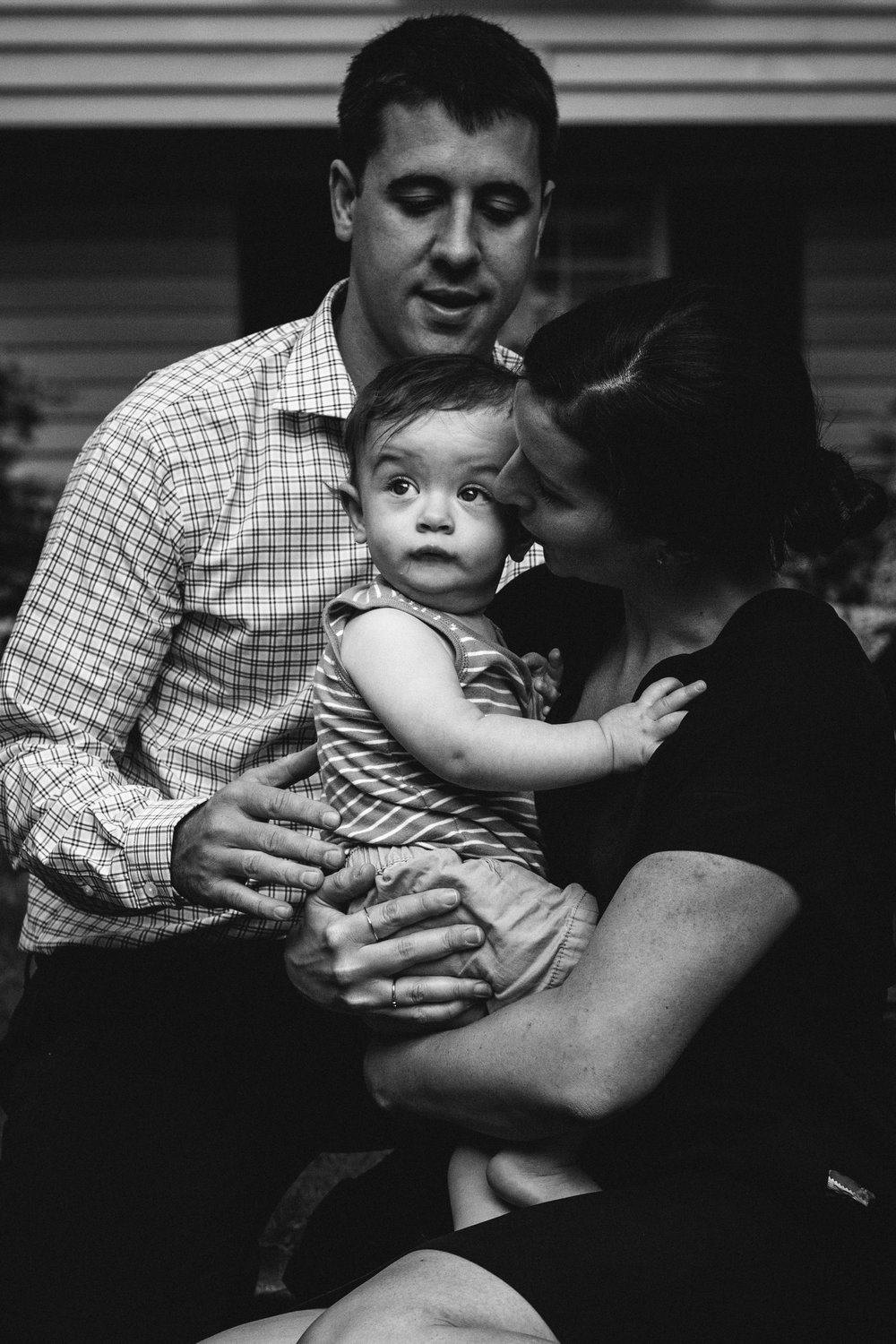 black and white photograph of parents cuddling baby son